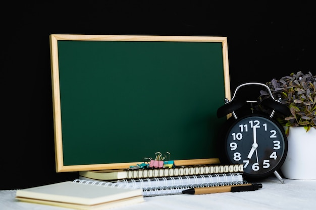 Green chalkboard with pile of notebooks and alarm clock