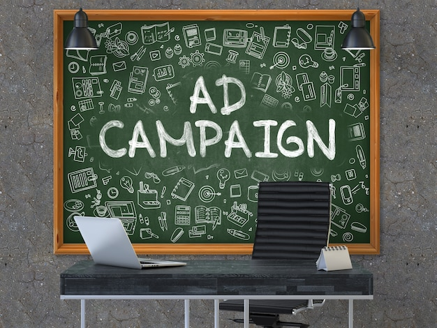 現代のオフィスの内部にある暗い古いコンクリートの壁に、テキスト広告キャンペーンのある緑の黒板がぶら下がっています。