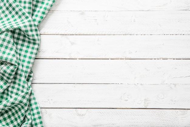 Зеленая клетчатая кухонная скатерть на деревянном столе.