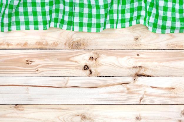 Зеленая клетчатая скатерть на светлом деревянном столе, вид сверху