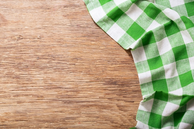 Зеленая клетчатая скатерть на деревянном столе, вид сверху