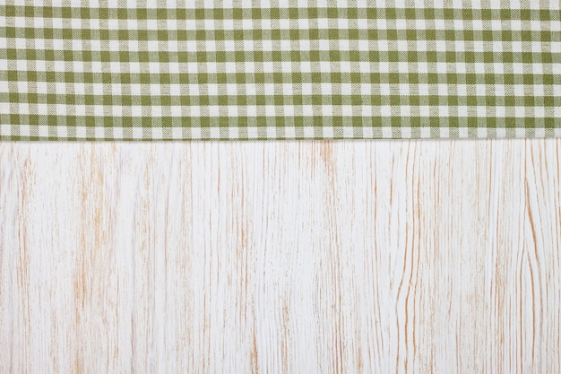 Green checkered tablecloth textile on white wooden table background. top view, flat lay with copy space, banner
