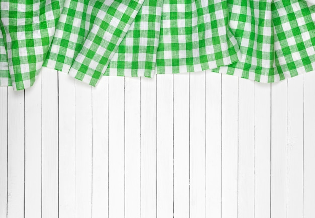 Green checkered tablecloth on wooden table, top view