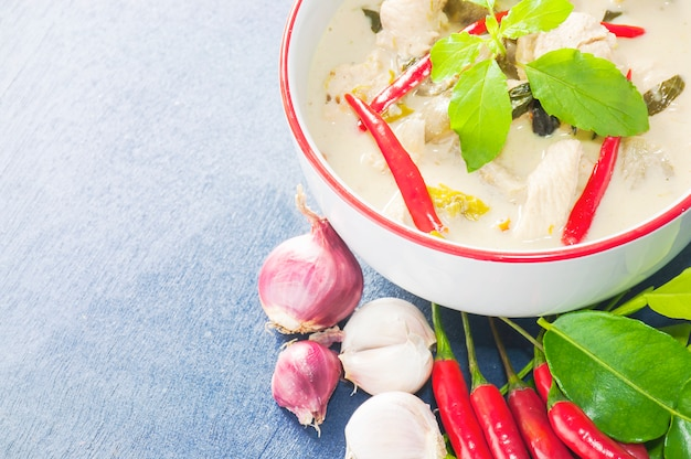 Green chicken curry with raw spicy ingredient thai traditional food on light blue background