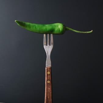 Green chili pepper in fork on black backdrop