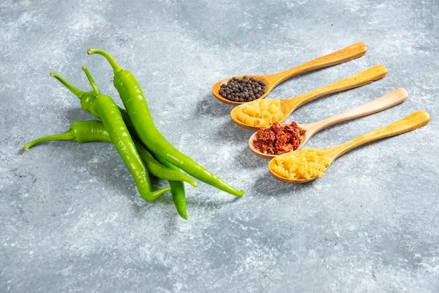 Зеленый перец чили и деревянные ложки макаронных изделий.