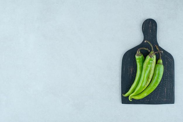 Зеленые перцы чили на темной доске.