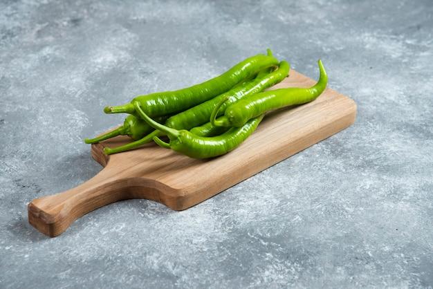 Зеленые перцы чили на деревянной доске.