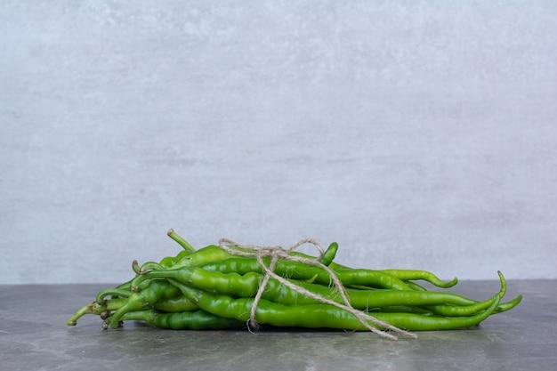 녹색 칠리 페 퍼 대리석 테이블에 밧줄으로 묶여.