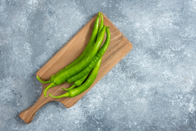 Green chili peppers on wooden board.