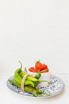 Green chilies and bowl of red tomatoes on ceramic plate against white background