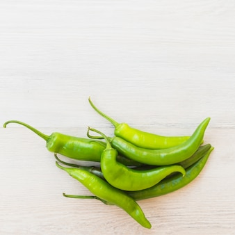 Green chilies on wooden background