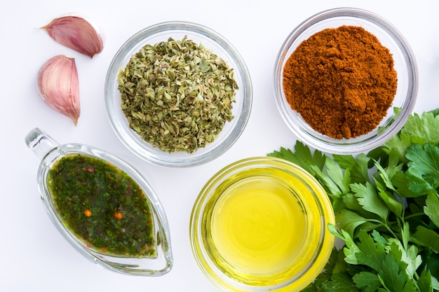 Green chimichurri sauce and ingredients isolated top view