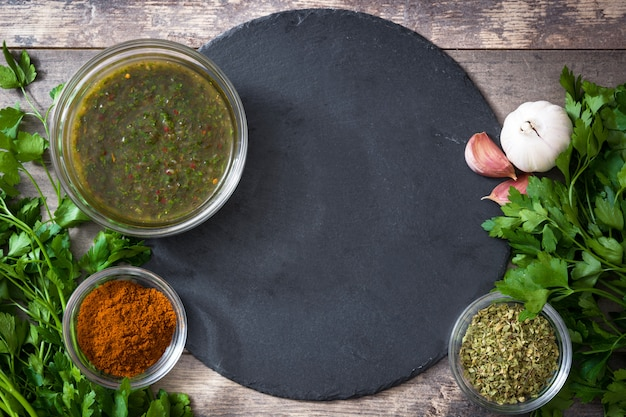 Green chimichurri sauce and ingredients on wooden table copy space