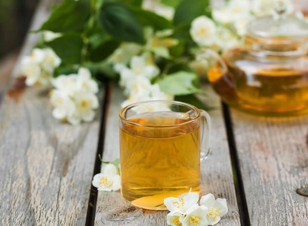 Green chinese tea with jasmine in a mug with jasmine flowers