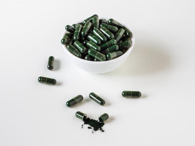 Зеленые таблетки хлореллы в белой миске на белом фоне