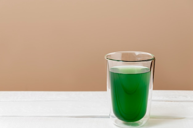 Green chlorophyll drink in a glass on white table with copy space