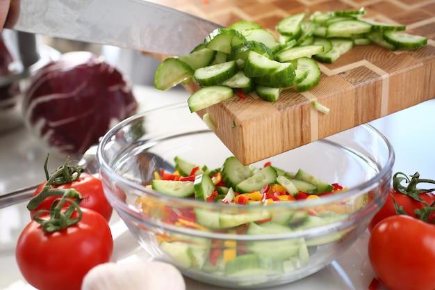Зеленые нарезанные ломтики огурца заливка стеклянной миски. ингредиент салата здоровой диеты.