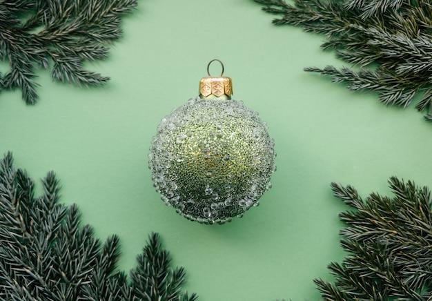 Зеленый елочный шар с шишками и еловой веткой на зеленом фоне минималистичный рождественский дизайн