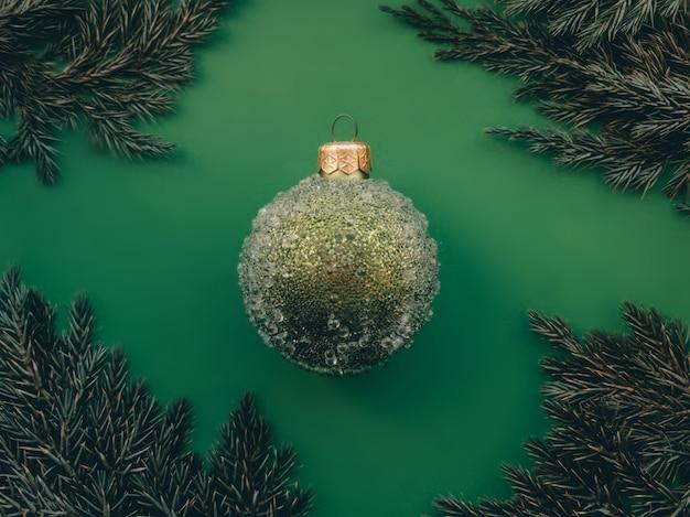 녹색 배경에 약간의 융기 및 가문비나무 나뭇가지가 있는 녹색 크리스마스 공 최소한의 크리스마스 디자인