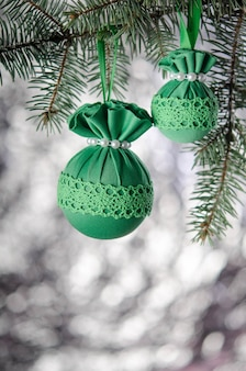 Green christmas balls on spruce branch on silver background new year decoration