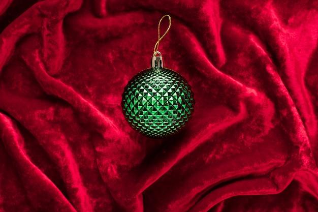 ドレープの赤いベルベット生地の緑のクリスマスの装飾