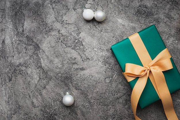 Green christmas gift on marble background with copy-space