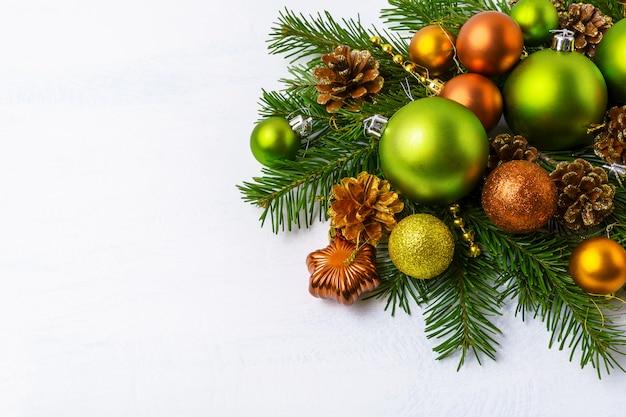 緑のクリスマス飾り、モミの枝、黄金の松ぼっくり、つまらない