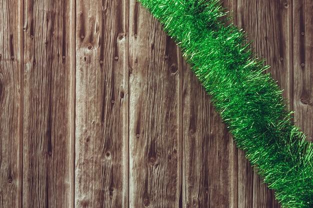 木製の背景に緑のクリスマスティンセル。スペースをコピーします。セレクティブフォーカス。