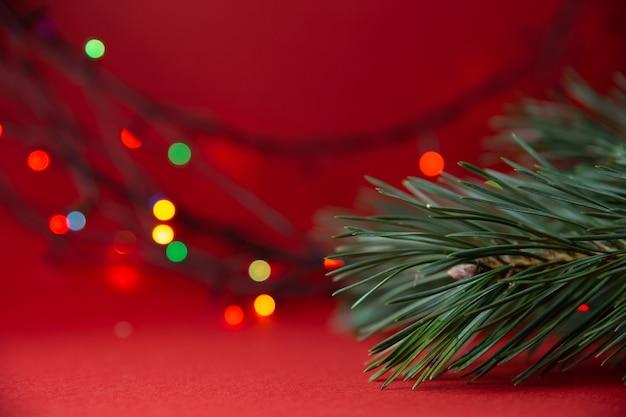 緑のクリスマスツリーの枝のクローズアップと赤い背景のボケ味でぼやけた明るい色とりどりのライトの花輪。クリスマス、新年を祝う。クリスマスの背景、ポストカード
