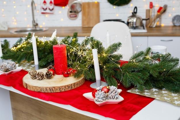 ボール、クリスマスの装飾、黄色の花輪で飾られた緑のクリスマスツリー。キッチンの新年の飾り。新年。クリスマスのための家の装飾。