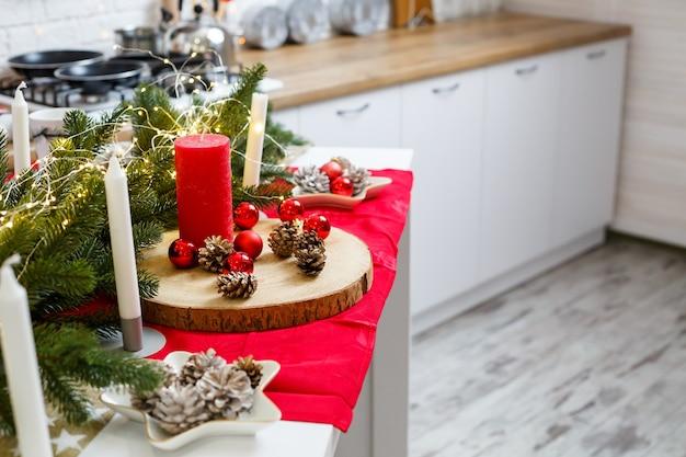 Зеленая елка, украшенная шарами, елочными игрушками, желтыми гирляндами. новогодние украшения на кухне. новый год. украшения в доме на рождество.