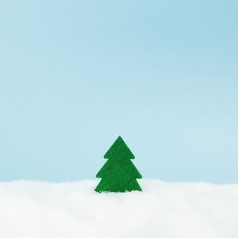 偽の雪と青い背景の上の緑のクリスマスツリー。