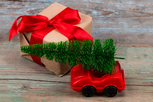 Зеленая рождественская елка на игрушечной машинке и подарке. концепция празднования рождественских каникул.