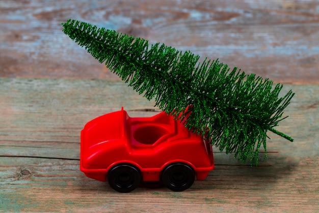 おもちゃの車の緑のクリスマスツリー。クリスマスの休日のお祝いのコンセプト