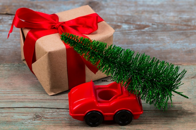 Green christmas tree on toy car and gift. christmas holiday celebration concept