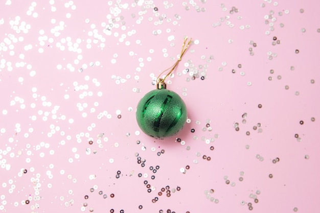 Green christmas tree toy on pink with glitters flat lay