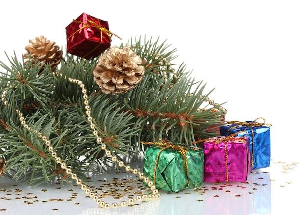 Зеленая рождественская елка с подарком и шишками, изолированными на белом
