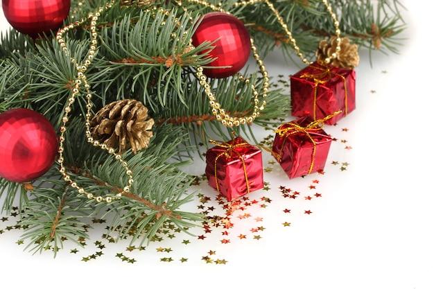 Зеленая рождественская елка с подарком, игрушкой и шишками, изолированными на белом