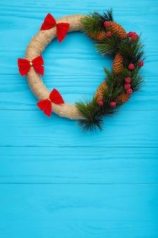 青い木製の背景に赤い弓で飾られた緑のクリスマスリース。感謝祭。上面図。