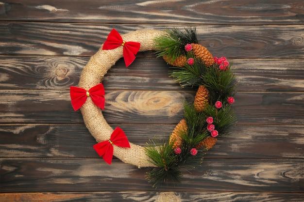 茶色の木製の背景に赤い弓で飾られた緑のクリスマスリース。感謝祭。上面図。