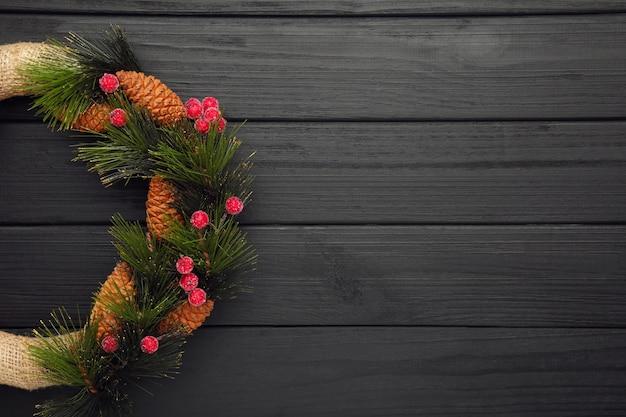 黒の木製の背景に赤いガマズミ属の木で飾られた緑のクリスマスリース。感謝祭。