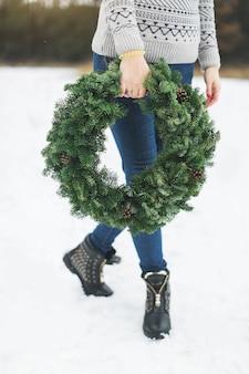 Зеленый рождественский венок на женских руках. женщина с рождественским венком гуляет в зимнем парке.