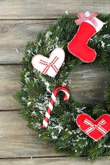 Зеленый рождественский венок с украшениями на деревянных фоне