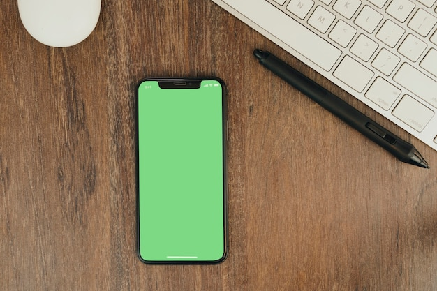 Green chroma key on smartphone screen on wooden background with a computer beside it.