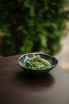 黒いボウルに緑の中華海藻サラダ