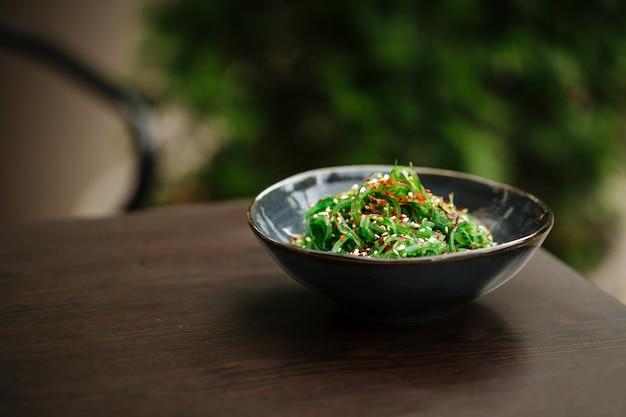 Салат из зеленых водорослей чука в черной миске