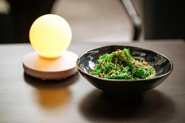 ランプとテーブルの上の緑の中華海藻サラダ