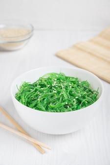 Салат из зеленых водорослей чука вакаме с кунжутом, подается в миске с бамбуковыми палочками на столе