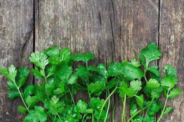 上面図の古い木製の背景に緑のコリアンダーの葉料理のための新鮮なコリアンダー
